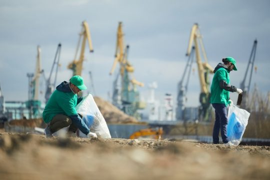 Two young men picking up litter on construction site and putting it into sacks